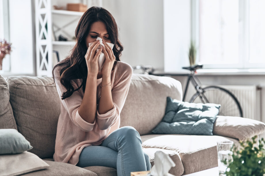 Sick young woman blowing the nose using tissue paper while sitting on the sofa at home
